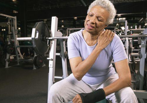 Senior woman in gym rubbing shoulder.