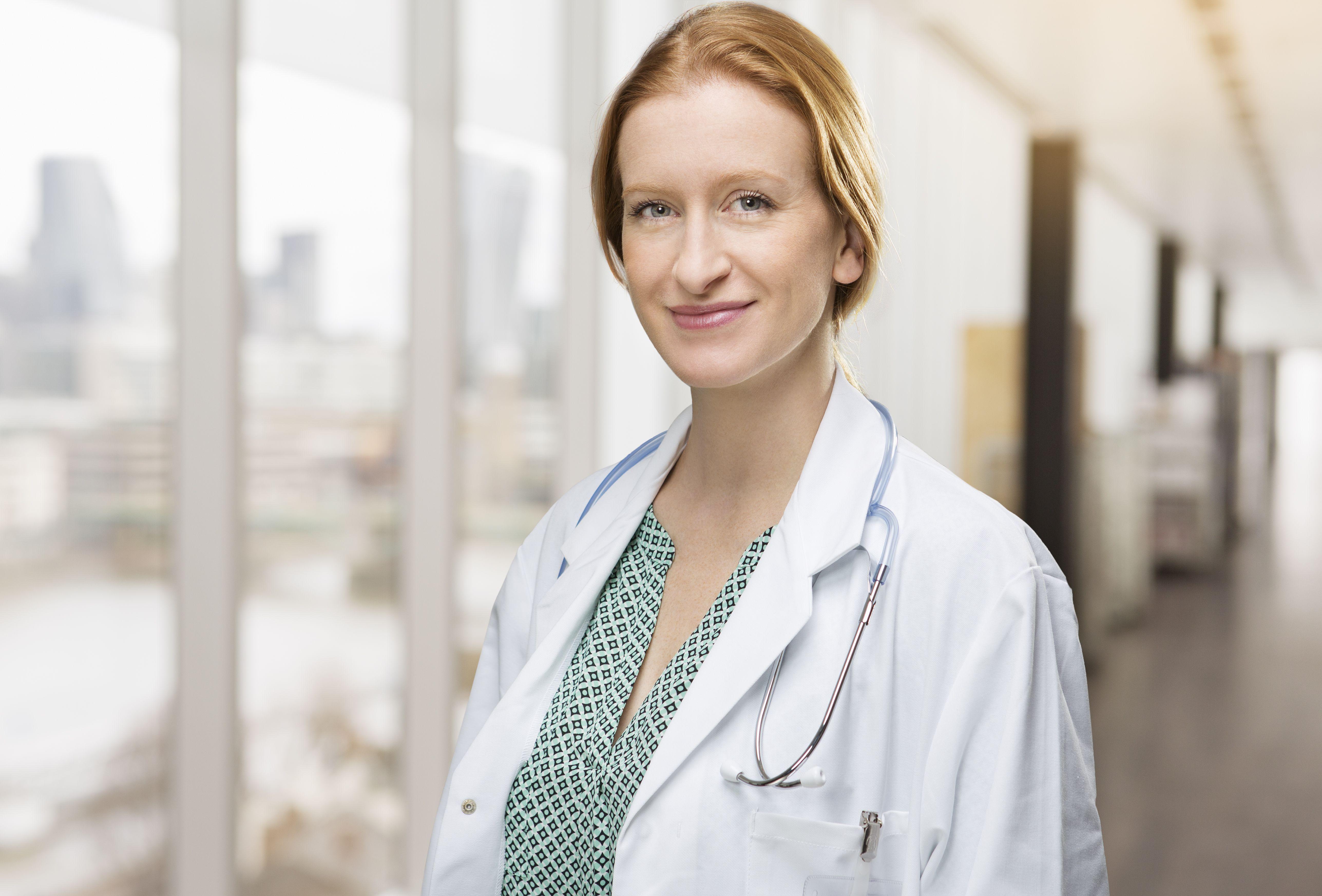 Portrait of female doctor in corridor in hospital.