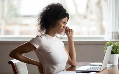 woman work at laptop suffer from spinal spasm