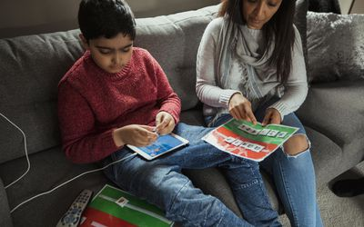 Mother and son using tablet and paper while doing son's autism therapy