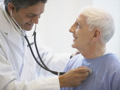 a doctor listening to the heartbeat of an elderly male patient
