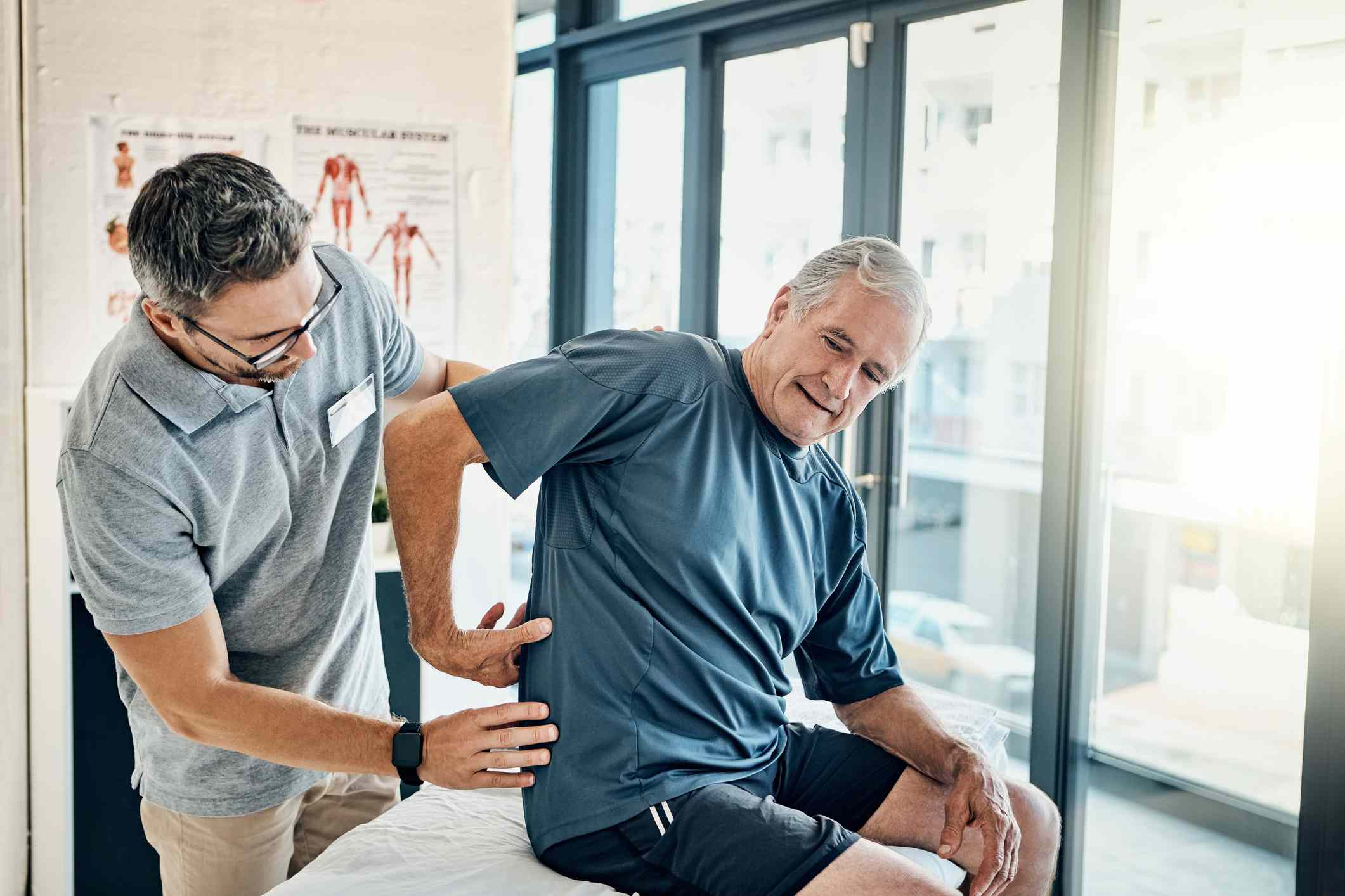 Man in physical therapy pointing to his low back.
