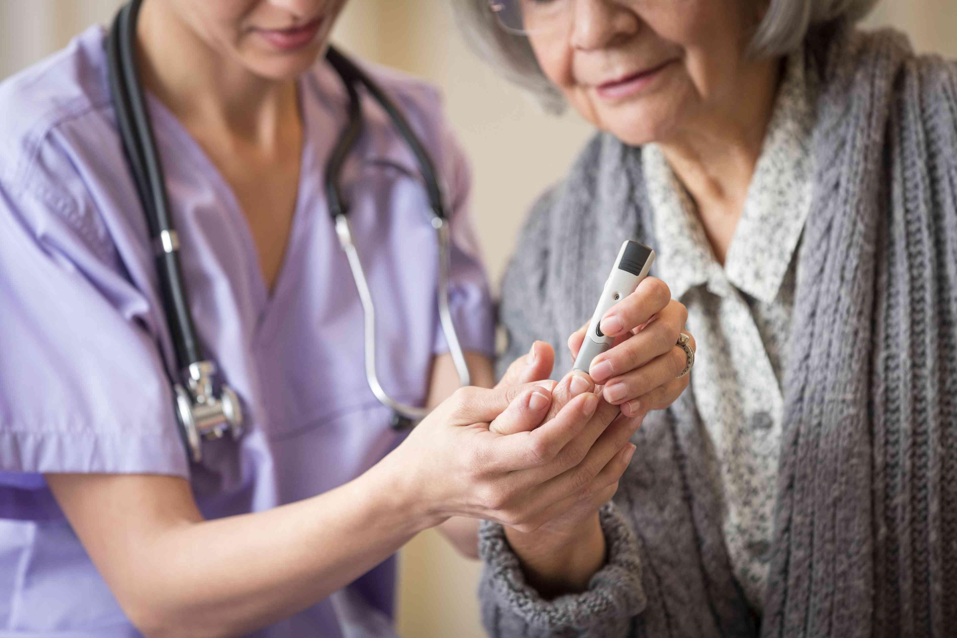 Photo of a nurse checking a woman's blood sugar