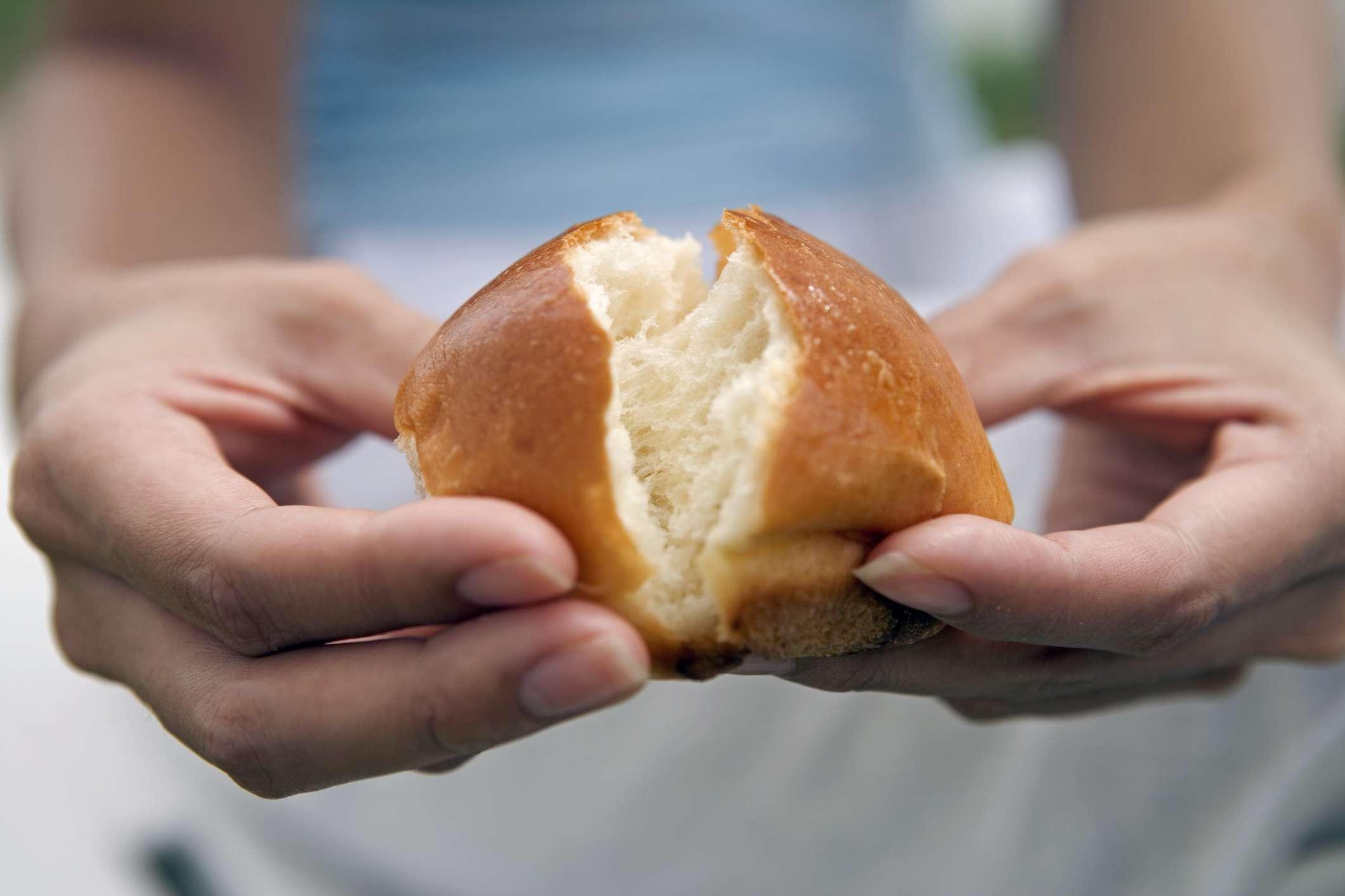 Woman's hands breaking bread