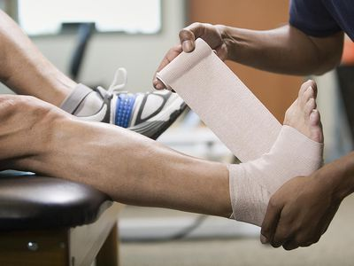 a physical therapist wrapping a man's foot in bandage