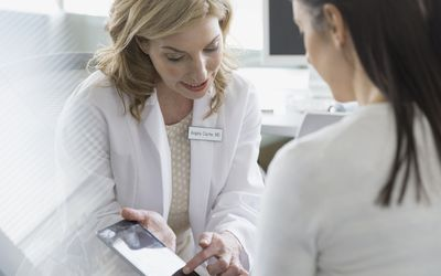 Doctor and patient looking at digital tablet