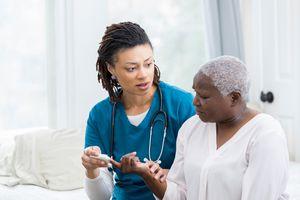 Concerned nurse checks patient's blood sugar