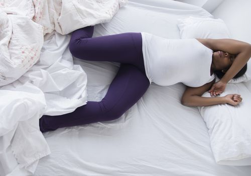 a pregnant woman laying in bed