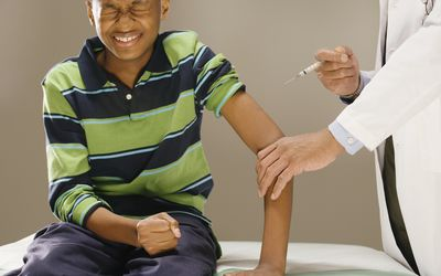 teenage boy bracing himself for injection from a doctor