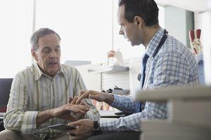Doctor examining senior patients hand in office.