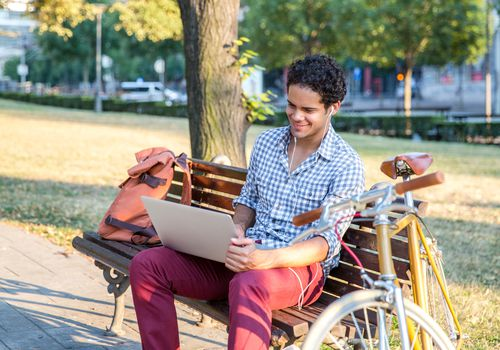 A man using a laptop in the park