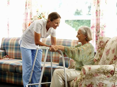 caretaker helping senior woman stand up from a chair.