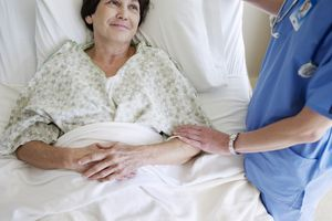 nurse comforting woman in hospital bed