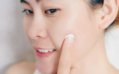 Woman applying acne cream to her her