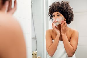 Teenager Applying Facial Mask While Looking In Mirror At Bathroom