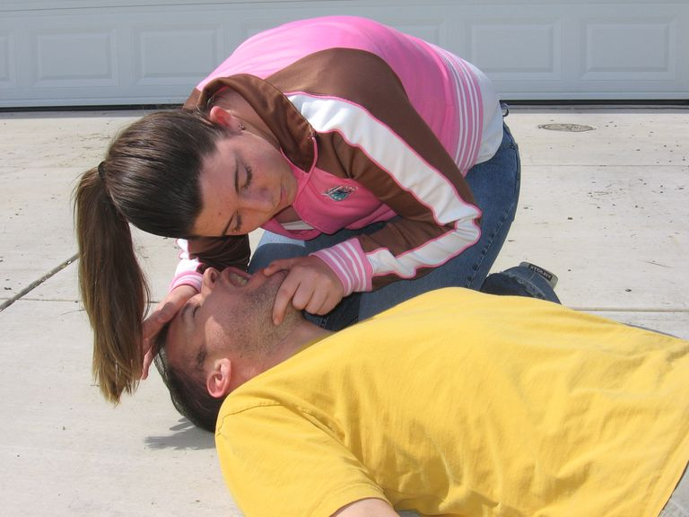 Woman performing CPR on man