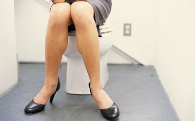 woman sitting on the lid of toilet