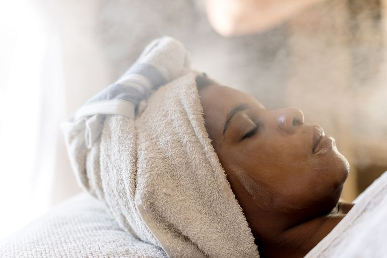 Woman with a towel wrapped around her hair getting a steam treatment