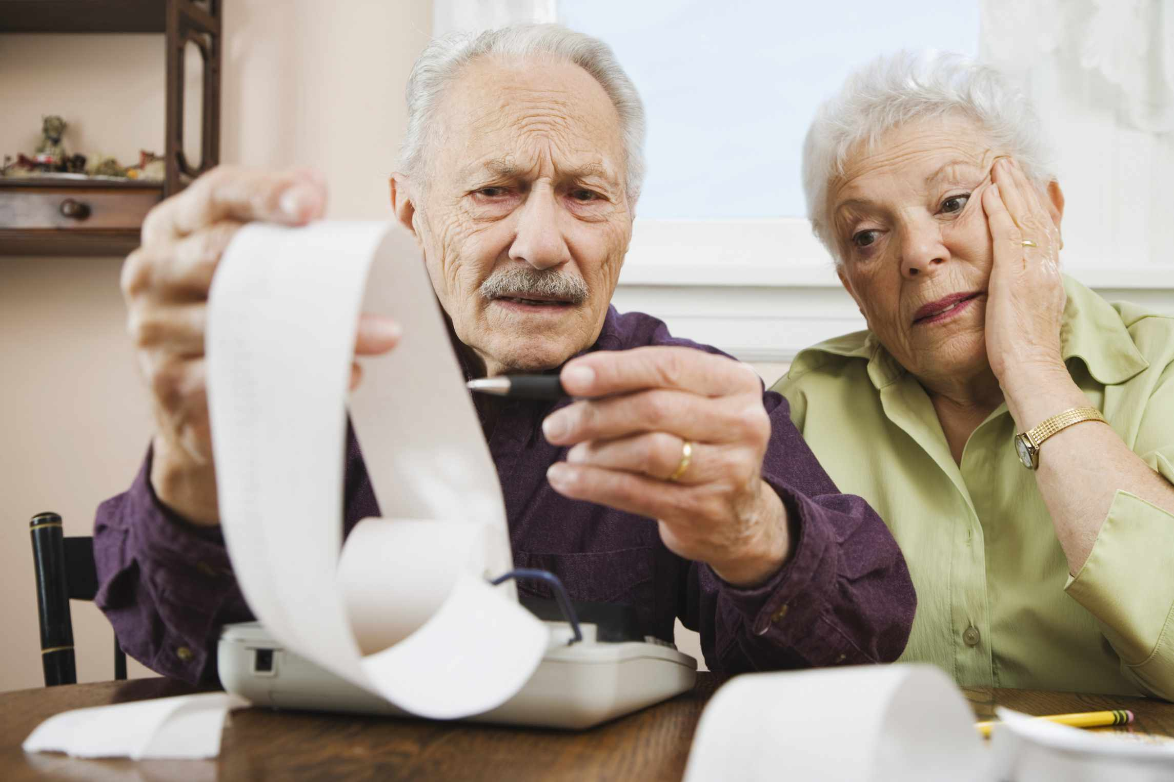 An older couple looking at a long receipt