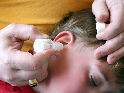 Adult administering ear drops to a child