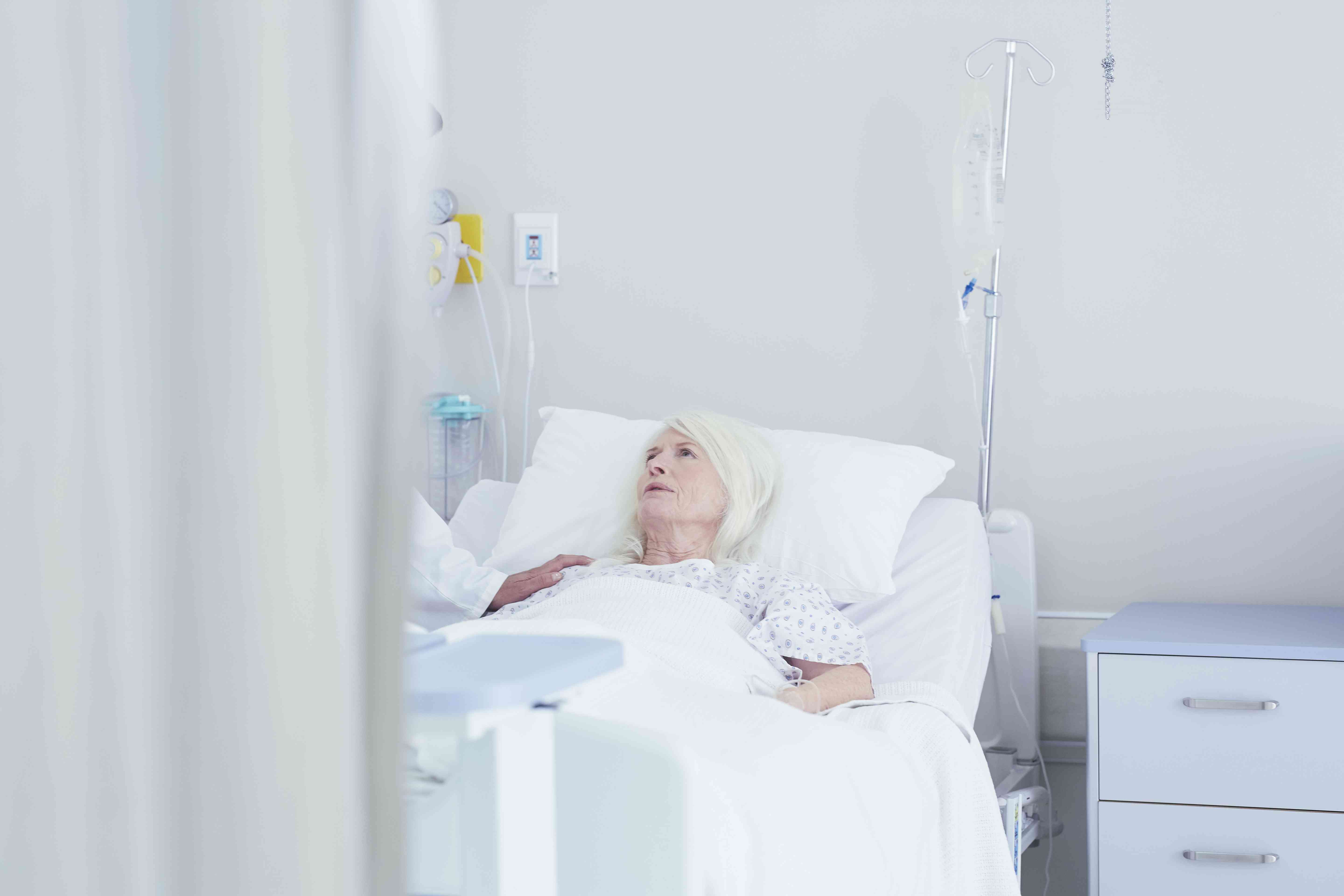 Doctor talking to worried senior female patient in hospital bed