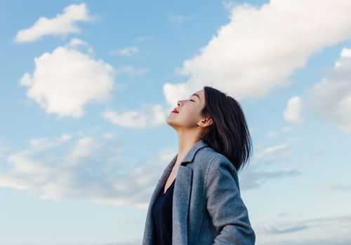Portrait of positive young Asian woman with eye closed, enjoying sunlight under blue sky and clouds.