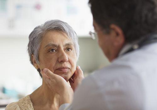 Doctor examines neck of female patient
