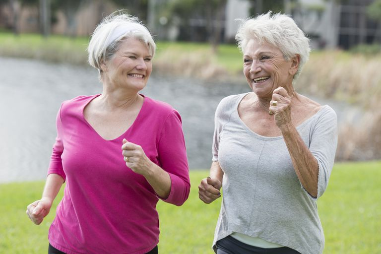 two elderly women power walking and smiling