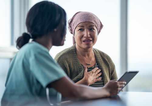 Woman with cancer discussing with nurse.