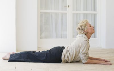 Mature woman doing cobra pose with eyes closed