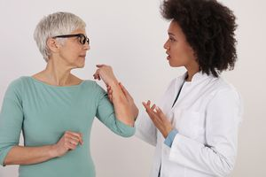 A Black female doctor examines a bruise on a woman's arm.