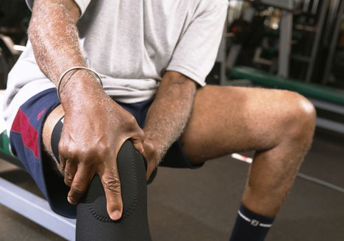 Man sitting in the gym holding his braced knee