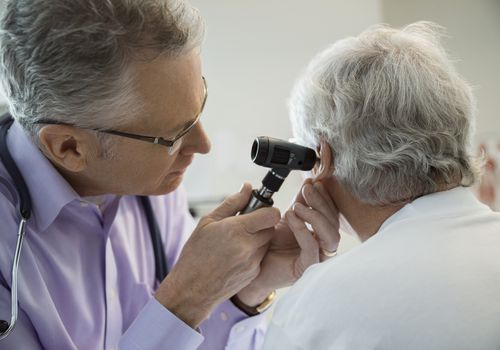 Doctor examining a senior man's ear