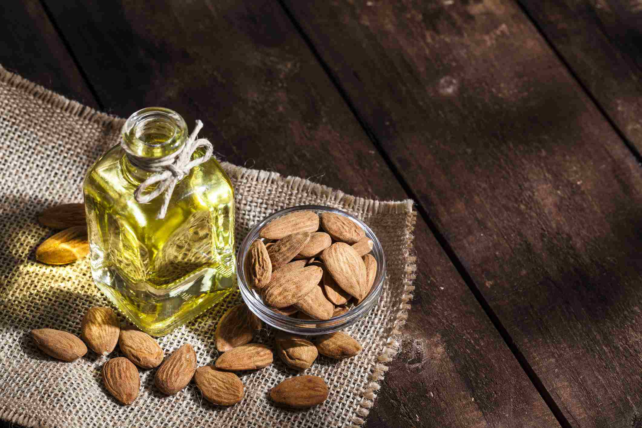 Almond oil and small bowl of almonds on table