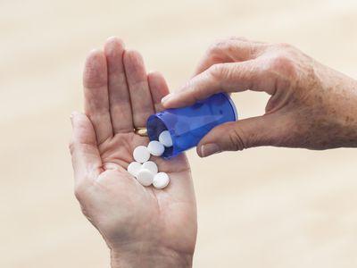 Senior woman holding prescription pills