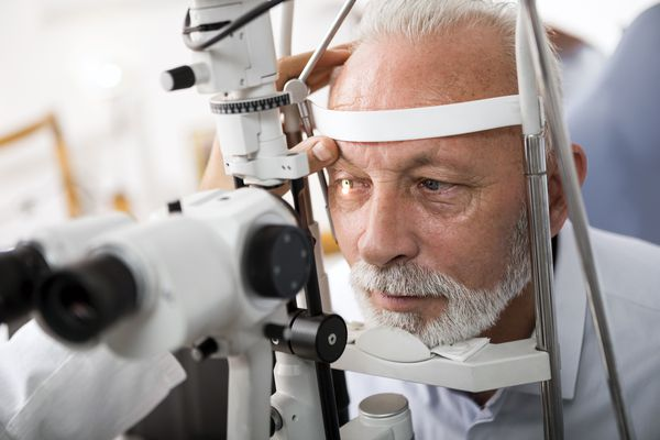 Senior man doing eye test with optometrist