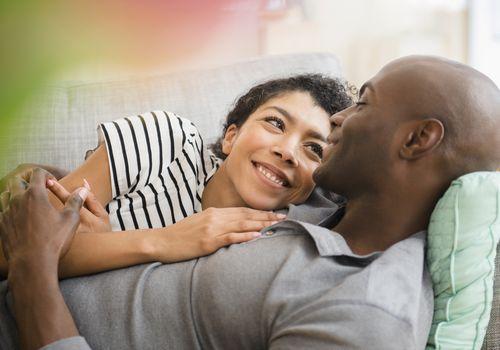 Smiling couple laying on sofa