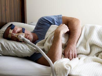 Man Sleeping in bed with sleep apnea mask on