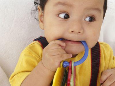 10 month old baby boy biting on teething ring