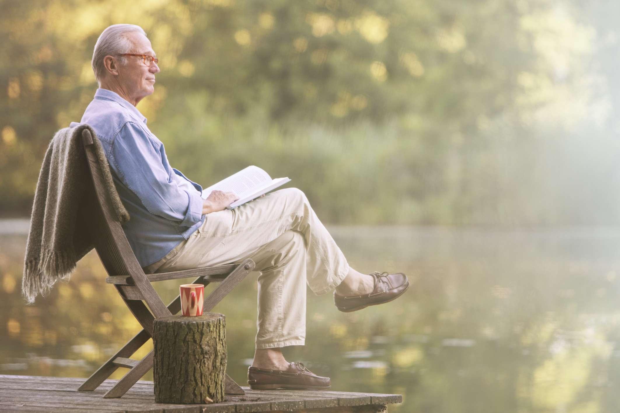 Man reading book on dock at lake