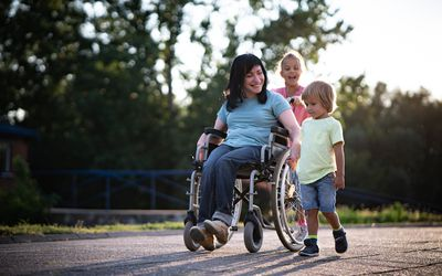 Mother in wheelchair whit her children spending time outdoors