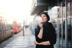 Front view portrait of woman on train station, smoking cigarette