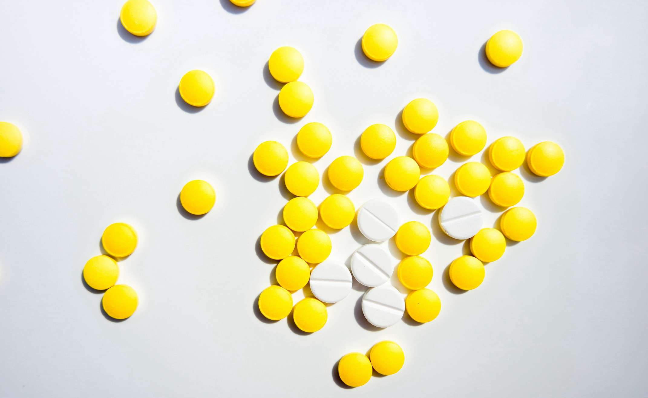 Yellow and white pills on a white background