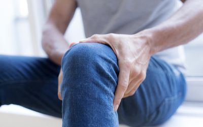 Man holding his left knee in pain