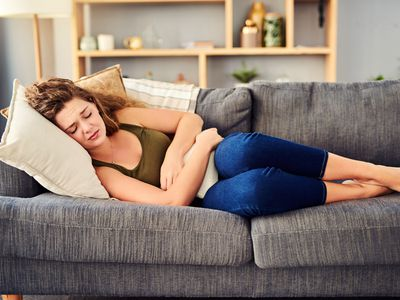 Woman lying on a couch in discomfort