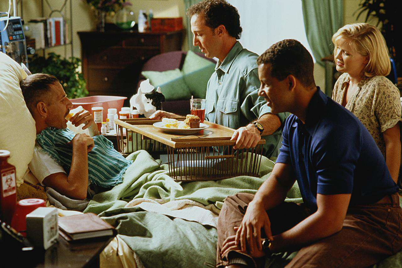 People gathered around a sick man in bed at home