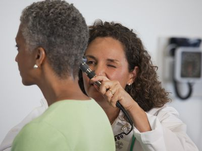 Adult woman being checked for an ear infection.