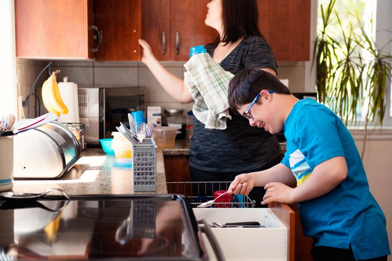 A son doing the dishes with his mother