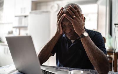 Worried senior man working at laptop
