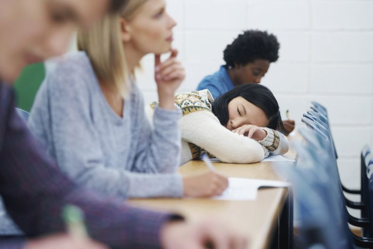 asian woman sleeping on desk as other students pay attention
